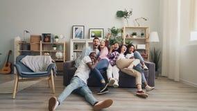 Langzaam motieportret van de blije jeugd die aan bank lachen meeslepen die camera bekijken stock videobeelden