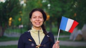 Langzaam motieportret van de charmante vlag die van de de ventilatorholding van meisjes Franse sporten van Frankrijk, en camera g stock video