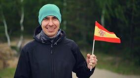 Langzaam motieportret van de glimlachende jonge mens die Spaanse vlag houden en camera bekijken die zich dichtbij groen bos bevin stock video