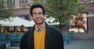 Langzaam motieportret van de knappe Afrikaanse Amerikaanse mens in glazen in openlucht stock videobeelden