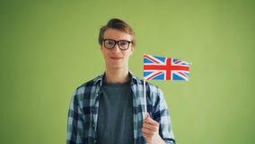 Langzaam motieportret van de knappe jonge mens die het Britse offici?le vlag glimlachen houden stock footage