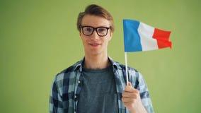 Langzaam motieportret van de vlag van de hipsterholding van Frankrijk en alleen het glimlachen stock videobeelden