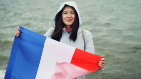 Langzaam motieportret van de vrolijke Franse officiële vlag van de patriotholding van Frankrijk met leuke glimlach die zich dicht stock footage