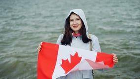 Langzaam motieportret van de vrolijke jonge holding die van de dame trotse burger Canadese vlag fladderen en het bekijken camera  stock videobeelden
