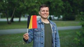 Langzaam motieportret van emotionele kerel met expressief gezicht die Belgische vlag, het bekijken camera en het glimlachen golve stock video
