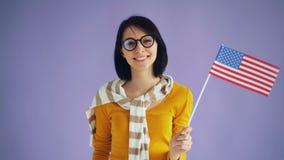 Langzaam motieportret van gelukkig Amerikaans meisje die vlag en het glimlachen van de V.S. golven de offici?le stock video