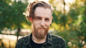 Langzaam motieportret van gelukkige gebaarde kerel hipster in militaire stijlkleding die zich in het park bevinden die en glimlac stock videobeelden