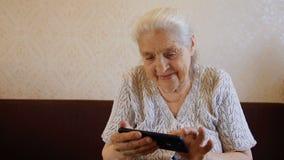 Langzaam motieportret van gelukkige oude vrouw die smartphone en het glimlachen gebruiken stock videobeelden