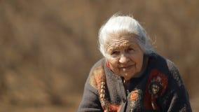 Langzaam motieportret van gelukkige oude vrouwenzitting in park en het glimlachen stock videobeelden