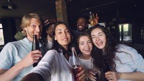 Langzaam motieportret van groeps mensen medewerkers die selfie met dranken bij bureaupartij, aantrekkelijke mannen en vrouwen nem stock video