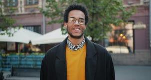 Langzaam motieportret van het gelukkige Afrikaanse Amerikaanse student glimlachen die zich in openlucht bevinden stock footage