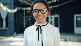 Langzaam motieportret van het jonge Afrikaanse Amerikaanse student in openlucht glimlachen stock footage