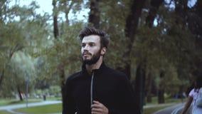 Langzaam motieportret van het Kaukasische mens lopen Sluit omhoog het knappe zakenman nadenken en het uitwerken in stil park stock video