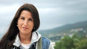 Langzaam motieportret van hipster vrouwelijke toerist status op piek van berg stock video
