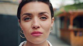 Langzaam motieportret van jonge volwassen vrouw met ernstig gezicht die zich in openlucht bevinden stock videobeelden