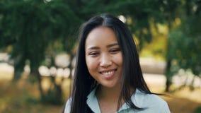 Langzaam motieportret van knap Aziatisch meisje met lang haar die lichtblauw overhemd dragen die zich in het park, het glimlachen stock footage