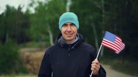 Langzaam motieportret van knappe de holdingsvlag die van de kerel Amerikaanse burger van de Verenigde Staten, en camera glimlache stock footage