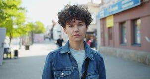 Langzaam motieportret van knappe jonge vrouw status buiten in de straat stock videobeelden