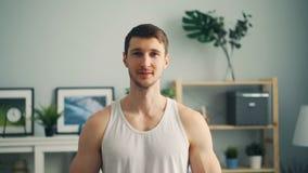 Langzaam motieportret van knappe sportieve kerel die thuis het bekijken camera glimlachen stock videobeelden