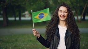 Langzaam motieportret van leuke Braziliaanse sportenventilator die camera, het golven van nationale vlag van Brazilië en het lach stock videobeelden