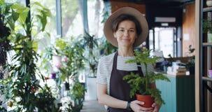 Langzaam motieportret van leuke jonge dame die ingemaakte installatie in de opslag van de bloemist houden stock footage