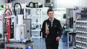 Langzaam motieportret van mannelijke ingenieur in fabriek die naar camera lopen stock footage