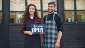 Langzaam motieportret van mooie dame en de haar partner knappe mens die open teken houden die klanten ongeveer informeren stock video