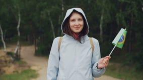 Langzaam motieportret van mooie jonge dame blije toerist die Braziliaanse vlag golven die in de wind, het glimlachen en het kijke stock video