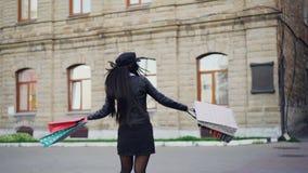 Langzaam motieportret van vrolijk Aziatisch meisje met het winkelen zakken die in openlucht in de straat in zich het moderne stad stock videobeelden