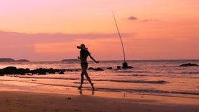 Langzaam motiesilhouet van gelukkige vrouw in hoed die op strand tijdens zonsondergang op vakantie lopen stock video