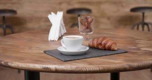 Langzaam op weg zijnd naar een restaurantlijst met een espresso en een croissant op het stock footage