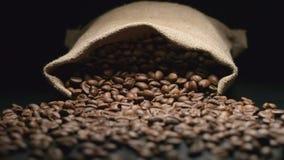 Langzaam: zakdalingen en van koffiebonen daling uit van hem stock footage