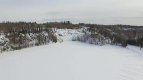 Langzame afdaling die aan snow-covered bevroren meer met rotsachtige heuvel op achtergrond landen stock video