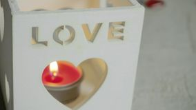 Langzame close-updia die van rode kaars in lantaarn met liefdetekst wordt geschoten op het Rood nam toe stock footage