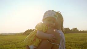 Langzame die motie van gelukkige moeder wordt geschoten die haar koesteren weinig babymeisje bij zonsondergang stock videobeelden