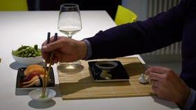 Langzame geanimeerde video van de mens met een baard die sushi eten en witte wijn drinken tijdens het diner stock footage