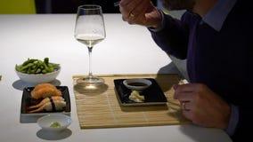 Langzame geanimeerde video van de mens met een baard die sushi eten en witte wijn drinken tijdens het diner stock videobeelden