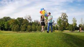 Langzame geanimeerde video van gelukkig jong paar die in park met bos van kleurrijke ballons lopen stock footage
