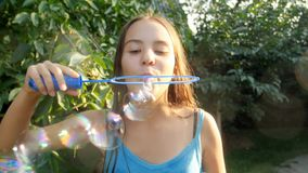 Langzame geanimeerde video van gelukkige het glimlachen bruntte meisjes blazende zeepbels in park bij zonnige dag stock footage