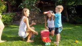 Langzame geanimeerde video van gelukkige kinderen die stuk speelgoed waterkanonnen vullen vanaf emmer bij binnenplaats stock video