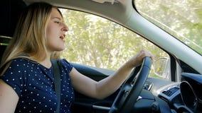 Langzame geanimeerde video van het gelukkige jonge vrouw zingen en het dansen terwijl het drijven van een auto op plattelandsweg stock footage