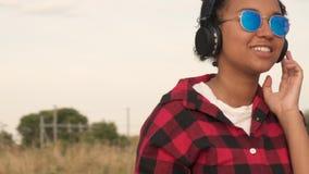 Langzame geanimeerde video van het mooie gemengde de tiener jonge vrouw van het ras Afrikaanse Amerikaanse meisje luisteren aan m stock video