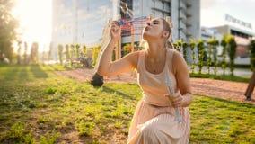 Langzame geanimeerde video van mooie jonge vrouwen blazende zeepbels in park bij zonsondergang stock video