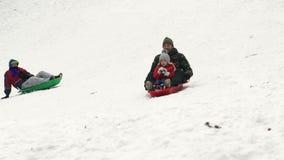 Langzame geanimeerde video van vader en dochter die op de sneeuwheuvel dalen met een slee, HD stock footage
