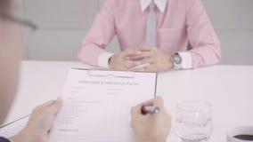 Langzame motie - Aantrekkelijke jonge Aziatische zakenman in een baangesprek met collectieve personeelschef die die zijn cv lezen stock videobeelden