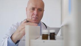 Langzame Motie Arts Looking aan een Medische Ontvanger en Studie een Zorgvuldig Voorschrift stock footage