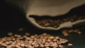 LANGZAME MOTIE: De daling van koffiebonen dichtbij een het liggen doekzak stock video