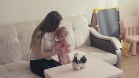 Langzame motie: De jonge aantrekkelijke moeder en een zoet kind breken een spaarvarken, dat van muntstukken volledig is stock footage