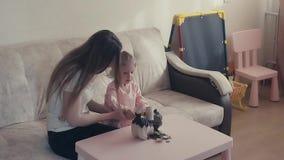 Langzame motie: De jonge aantrekkelijke moeder en het zoete kind breken een spaarvarken, dat van muntstukken volledig is stock footage