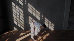 Langzame Motie De jonge Jongen treft voor een duel voorbereidingen Traditionele vechtsporten Hij buigt achteruit vooruit zijn rug stock videobeelden